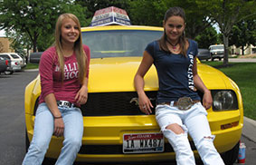 two girls on yellow car